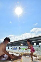 強い日差しが照りつける中、海水浴を楽しむ人たち=16日午後、那覇市・波之上ビーチ(金城健太撮影)