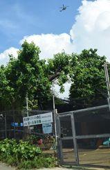緑ヶ丘保育園の園庭上空を飛行する米軍ヘリ=5日午後4時ごろ、宜野湾市野嵩