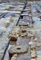 久茂地尋常小学校の土台となり、柱などを支えた石=13日、久茂地小学校運動場跡地