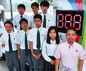 南部九州総体のカウントダウンボードを制作した沖縄工業高の生徒と、ポロシャツをデザインした小林憂菜さん(右から2人目)、平敷昭人県教育長(右)=8日、那覇市・パレットくもじ前広場