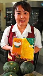 「つかざん完熟かぼちゃ」規格外品の加工商品を持つ大城清美さん=14日、南風原町津嘉山