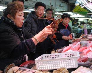 (資料写真)外国人観光客にイセエビを売る女性=1月11日、那覇市の公設市場