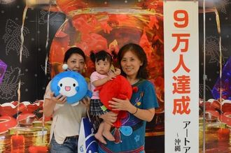 9万人目の来場となった(右から)前泊朋子さん、辺土名涼羽ちゃん、辺土名優美子さん=9日、那覇市のデパートリウボウ