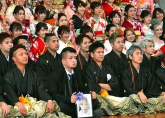 泉聖也さんの遺影と記念撮影に臨む大田凌弥さん(前列左から2人目)=13日、那覇市