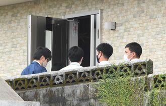 元タイムス社員の自宅を家宅捜索する沖縄県警の職員ら=13日午後2時ごろ