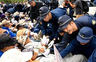 座り込む市民を強制排除する機動隊員=9月、東村高江