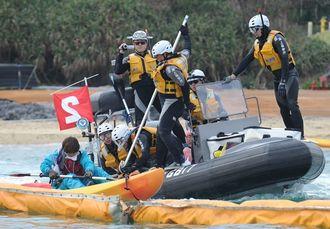 オイルフェンスの中に入った反対住民のカヌーを拘束しようとする海上保安庁のボート=2015年1月16日、沖縄県名護市辺野古