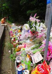遺体の遺棄現場には供花する人が絶えない=26日午前11時25分、恩納村安富祖