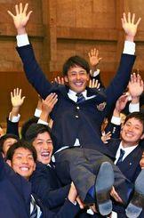 日本ハムに1位指名され、胴上げされる明大の上原健太投手=22日午後、東京都府中市