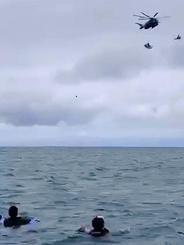 シュノーケリング中の観光客らの上空を通過するつり下げられた機体。本紙に寄せられた動画には、この後さらに観光客らに接近する様子が映る=11日午前9時40分ごろ(読者提供)