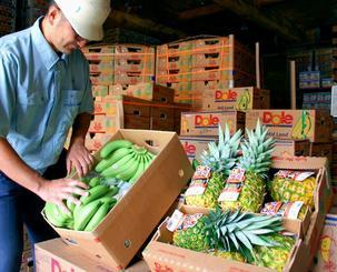 旧盆向けに輸入したバナナとパイナップル=17日、那覇青果物卸商事業協同組合