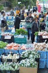 南部から北部までのファーマーズが集まった即売所で花や野菜を買い求める来場者=6日午前、那覇市・奥武山運動公園