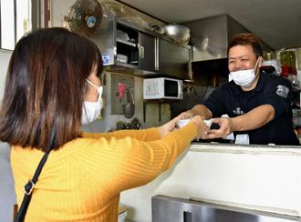 客に弁当を手渡す宜保政紀さん(右)=16日、豊見城市上田の「おべんとう屋・宜保商店」