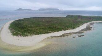 リーフと白い砂浜に囲まれた入砂島。奥に見えるのは渡名喜島=2018年
