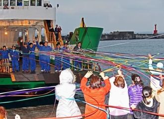 宮古島に向けて出港する最後のフェリーはやてを5色のテープで見送る伊良部の島民ら=佐良浜港