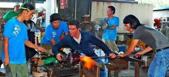 ベネチアガラスの技術を披露するシモネー・チェネデェーゼ氏(中央)、土田康彦氏(右)、琉球ガラス工芸協業組合の職人たち=5日、糸満市の琉球ガラス村工房