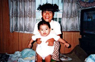 8歳の頃の玉城歩。当時0歳だった大切な妹の世話をする(本人提供)