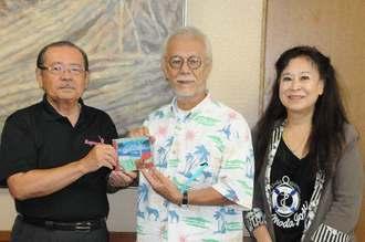長濱政治副市長(左)に「バラが咲いた」のハワイ語版をプレゼントする歌手のマイク眞木さん(中央)ら=6日、宮古島市役所