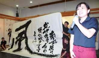 作品を掲げ、あいさつする玉城千博さん(右端)