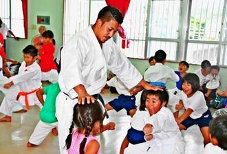 喜友名選手(中央)から空手を教わる子どもたち=15日、沖縄市・大里公民館
