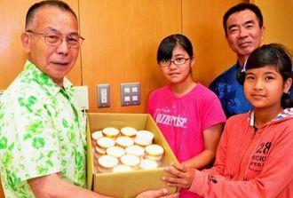 山川代表(左)からシークヮーサージェラートを受け取る(左2人目から)仲兼久さん、宮城校長、古堅さん=名護市・安和小学校