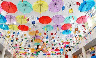 天井を彩る175本の傘。買い物客が撮影していた=28日、糸満市・糸満市場いとま~る(小宮健撮影)