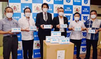 嘉手納町の當山宏町長(左から2人目)にマスクを寄贈したローテグループの長澤一輝上席執行役員ら=1日、町役場