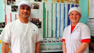 完食シールを貼る表の前に立ち、「楽しい給食時間を過ごしてほしい」と話す栄養士の桃原香苗さん(右)と調理員の翁長篤司さん=15日、諸見小学校