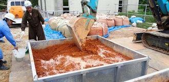 パワーショベルでかき混ぜられる泡盛粕の入った汚染土=2014年1月、うるま市内(提供)