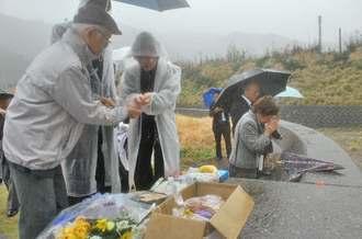 奄美大島に漂着した犠牲者を悼んで手を合わせ、米や水を供える生存者や遺族ら=18日、大和村の今里漁港