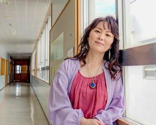 母校・読谷中学校の廊下に立つ玉城千春さん