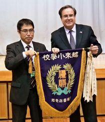 優勝旗の返還を喜ぶ越来小の高江洲実校長(左)と仲介したマグルビー米総領事=同小体育館