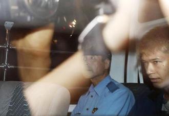 2016年7月、報道陣が取り囲む中、警察車両で相模原・津久井署に入る植松聖被告(右)