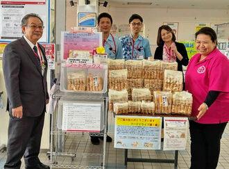 フードドライブに寄付した久高彩さん(右)と石川郵便局の平安山英孝局長(左)ら=23日、うるま市・石川郵便局