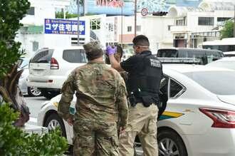 強盗事件に関与したとみられる米軍関係者の男(中央)が沖縄署へ連行される=15日午後1時55分ごろ
