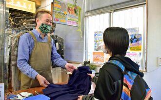 学生服を持ってきた中学生に笑顔で対応する「日琉舎ランドリー」店主の宜保直樹さん(左)=26日、豊見城市高嶺