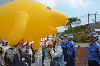 ジュゴンの風船を押し立てて基地に向かって抗議する市民ら=30日午前11時21分、名護市辺野古のキャンプ・シュワブゲート前