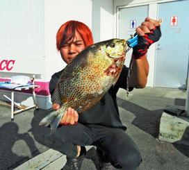 恩納村海岸で40センチ、1・42キロのカーエーを釣ったチームOPCの小濱裕士さん=3日
