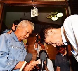 土地所有者の西銘晃さん(左)に頭を下げる沖縄防衛局の鍋田克己管理部次長=11日午後10時47分、東村高江