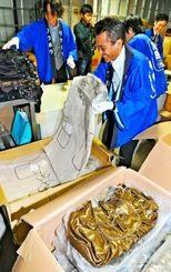バッグやコートなどを手際よく福袋に詰めるリウボウ職員=29日午前、那覇市のパレットくもじ