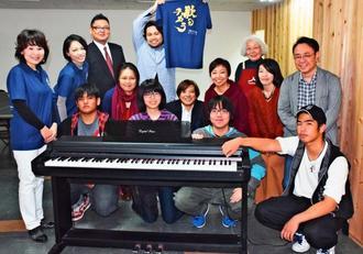 電子ピアノを寄贈した森の音楽館の喜納留美子副館長(左)ら関係者=9日、那覇市牧志「kukulu」