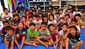 長若道代主任支援員(最後列中央)となはっ子児童クラブの子どもたち=25日、那覇市前島