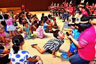 ファミリー吹奏楽団ビビデバビデブーの演奏に合わせて歌う子どもたち=4日、那覇市久茂地・タイムスホール(金城健太撮影)