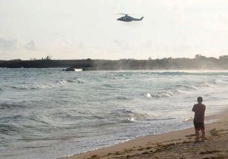シュノーケリングをしていた家族が流された現場付近を捜索する海上保安庁のヘリコプター=2015年