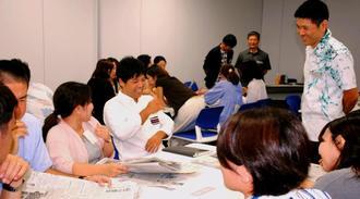 新聞記事を読み、感想を共有する「おきなわNIEセミナー」の参加者=26日、沖縄タイムス社