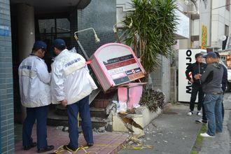トラックが衝突した現場を調べる警察官ら=4日午前8時15分ごろ、浦添市屋富祖のテナントビル