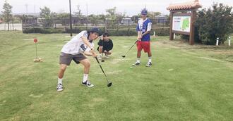 パークゴルフを楽しむ大学生=18日、読谷村座喜味のユンタンザパークゴルフ場
