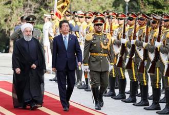 歓迎式典に臨む安倍首相。左はイランのロウハニ大統領=12日、テヘラン(共同)