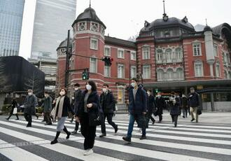JR東京駅前を歩くマスク姿の人たち=27日午前