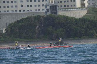 浜からフロートを伸ばし設置作業をする沖縄防衛局の作業船=15日午前9時12分、名護市辺野古